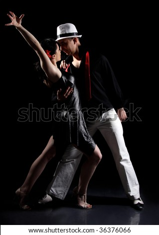 romantic tango dancing couple on black - stock photo