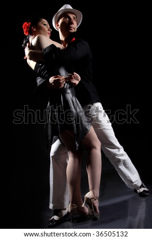 romantic tango dancing couple on black - stock photo