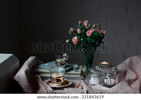 Romantic tea time settings with candles, roses, glass vases and other decorations, with window on the background. Natural light, toned photo. - stock photo