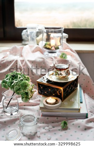 Romantic tea time settings with candles, roses, glass vases and other decorations, with window view on the beach on the background. Shallow focus. Natural light, toned photo. - stock photo