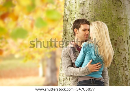 Romantic Teenage Couple By Tree In Autumn Park - stock photo