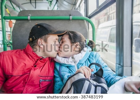 Romantic Teenage Couple Kissing inside public transport. passionate dating a beautiful young woman and man in the cabin of the bus.