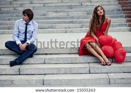 Romantic teenager couple in quarrel sitting on staircase - stock photo