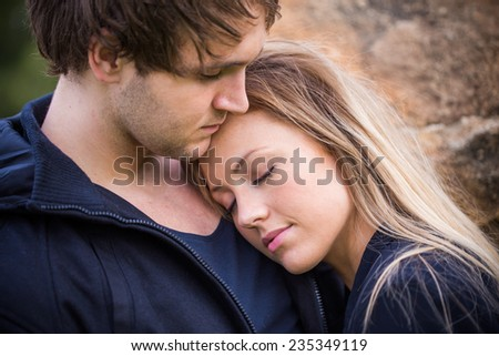Romantic, tender moment of a young attractive couple. Adorable girl closing her eyes on her boyfriend - stock photo
