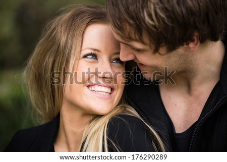 Romantic, tender moment of a young attractive couple. Cheerful girl close up portrait  - stock photo