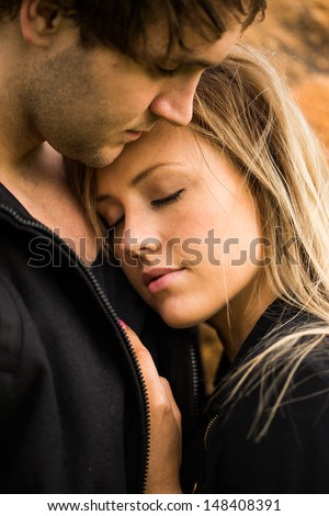 Romantic, tender moment of a young attractive couple. Pretty adorable girl closing her eyes - stock photo
