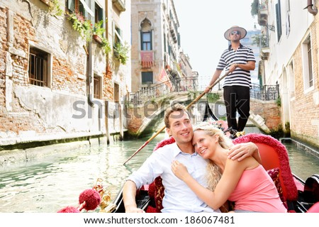 Romantic travel couple in Venice on Gondole ride romance in boat happy together on travel vacation holidays. Romantic young beautiful couple sailing in venetian canal in gondola. Italy, Europe. - stock photo