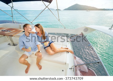 Romantic vacation and luxury travel. Young loving couple sitting on the sofa on the modern yacht deck. Sailing the sea. - stock photo