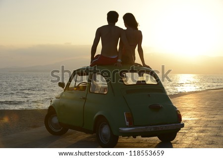 romantic vacation: couple at sundown on the beach with car - stock photo