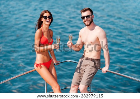 Romantic vacation. Happy young couple holding glasses with champagne while leaning at the handrail on yacht - stock photo