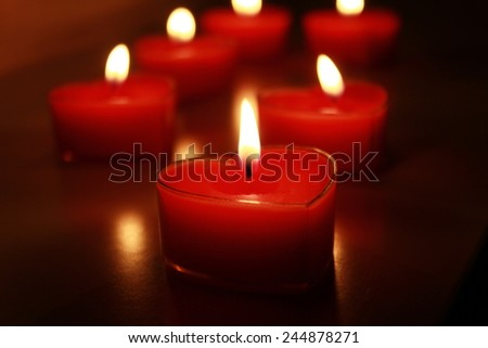 Romantic Valentine's evening with red candles in the shape of hearts