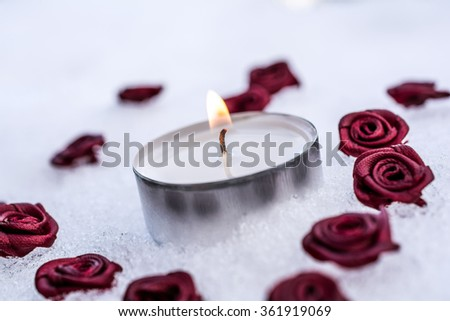 Romantic Valentine Tea Light On Ice Surrounded By Rose Bloom - stock photo