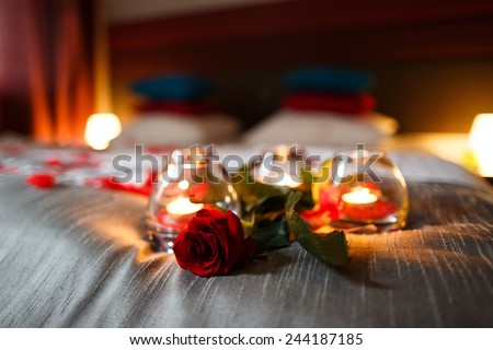 Romantic Valentines Day evening. Romantic night. Rose and candles on bed. - stock photo