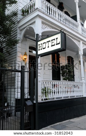 Romantic Victorian style hotel with a lit sign and porch - stock photo