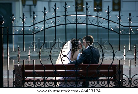 Romantic wedding couple sitting on a bench in the park - stock photo