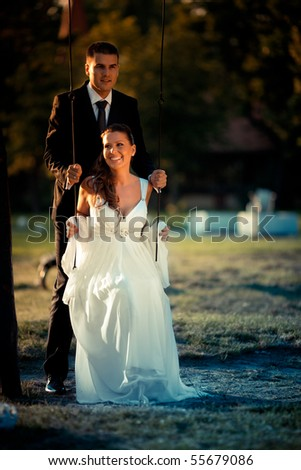Romantic wedding couple sitting on a swing in nature - stock photo