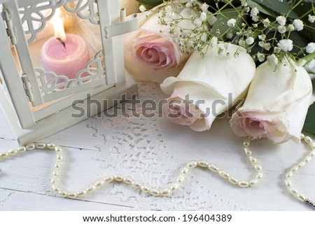 Romantic wedding still life with white roses, pearl necklace and burning candle in lantern - stock photo