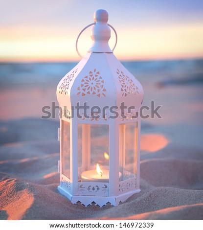 romantic white lantern on the beach - stock photo