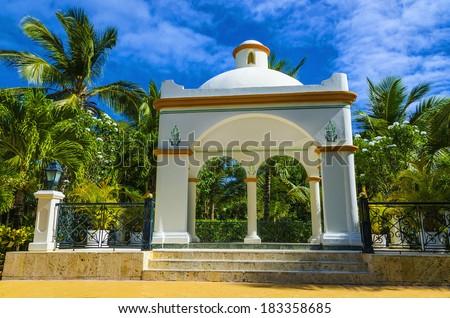 Romantic white wedding gazebo near the beach among palm tress on the Caribbean Islands - stock photo