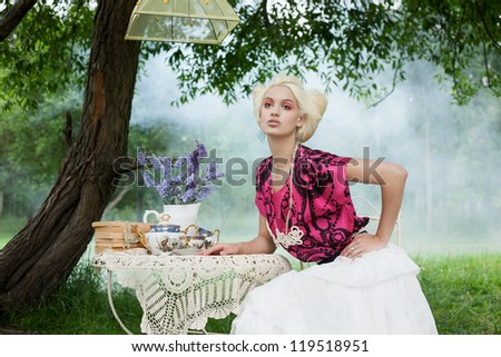 Romantic woman on a picnic in a fairy foggy forest. Outdoors. - stock photo