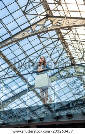 Romantic woman standing on balcony at railway station with glass ceiling