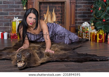 Romantic woman  under Christmas tree  lies on bearskin - stock photo