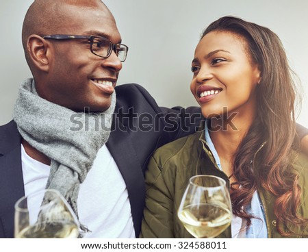 Romantic young African American couple sitting arm in arm enjoying glasses of white wine and smiling lovingly into each others eyes, close up view - stock photo