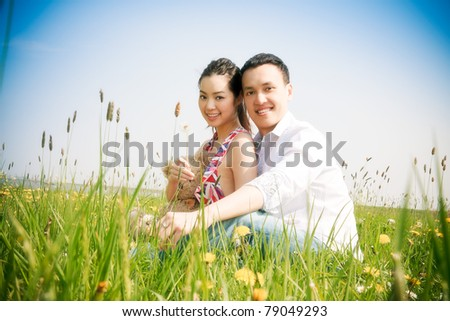 Romantic young asian couple in love in field of yellow flowers.
