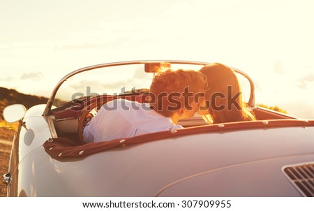 Romantic Young Attractive Couple Watching the Sunset and Kissing in Classic Vintage Sports Car - stock photo