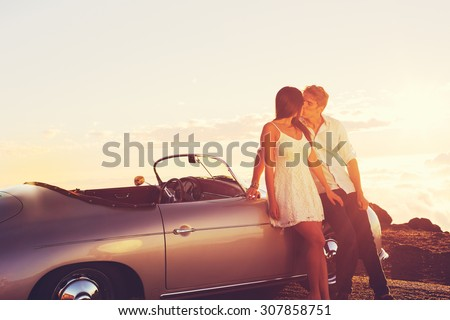 Romantic Young Attractive Couple Watching the Sunset and Kissing with Classic Vintage Sports Car - stock photo