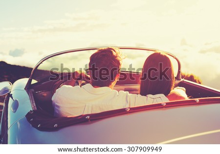 Romantic Young Attractive Couple Watching the Sunset in Classic Vintage Sports Car - stock photo