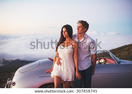 Romantic Young Attractive Couple Watching the Sunset with Classic Vintage Sports Car - stock photo