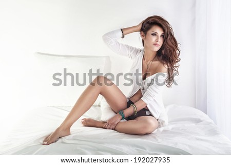 Romantic young beautiful brunette woman posing , sitting on big white bed - stock photo