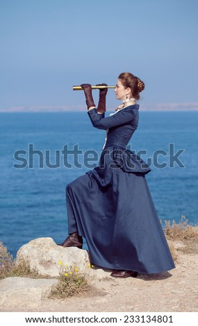 Romantic young beautiful lady looks at spyglass outdoors    - stock photo