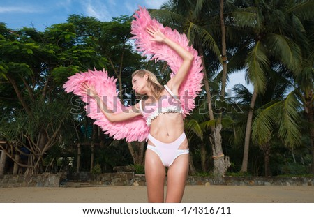 Romantic young beauty as an angel on the tropical beach. Blonde pretty female woman wearing pink wings, feather bra and bikini bottom standing on the tropical beach over green palm trees background