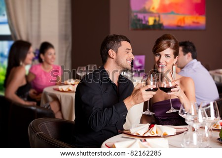 romantic young couple at restaurant table toasting - stock photo