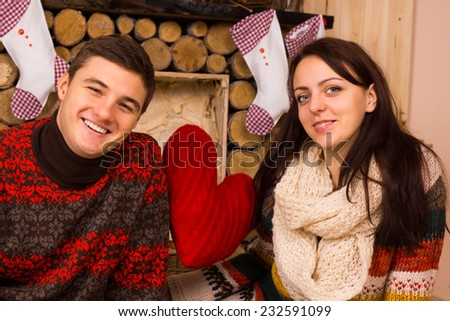 Romantic young couple celebrating Christmas in a rustic wooden cabin decorated with traditional Xmas stockings and a big red heart - stock photo