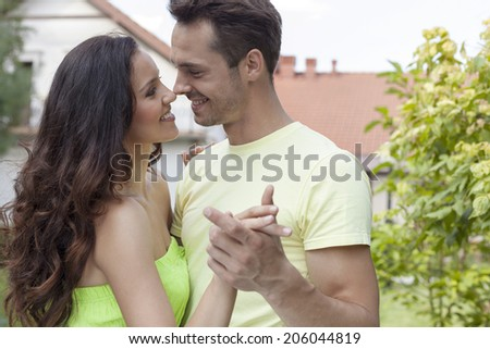 Romantic young couple dancing in park - stock photo
