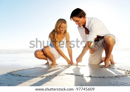 Romantic young couple draw heart shapes in the sand while on honeymoon. summer beach love concept.