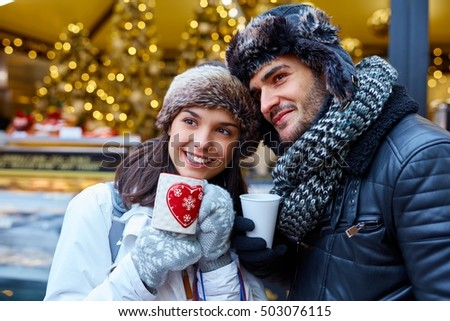 Romantic young couple drinking hot drink on the street at wintertime.