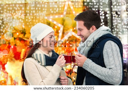 Romantic young couple drinking hot wine punch claret on christmas market - stock photo