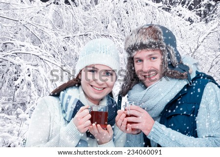 Romantic young couple drinking mulled wine in front of snowy forest - stock photo