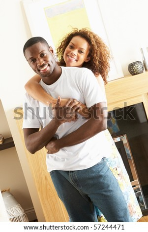 Romantic Young Couple Embracing In Living Room - stock photo