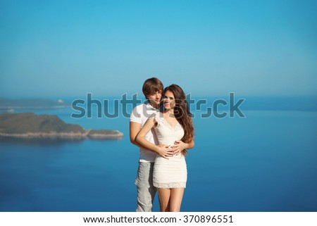 Romantic young couple embracing in love on vacation, over adriatic sea and blue sky. Wedding honeymoon Travel.  Exotic Island. - stock photo