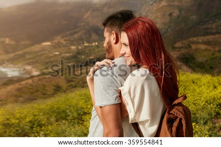 Romantic young couple enjoying the sights while hiking through the mountain. Young woman embracing his boyfriend from behind, while both looking at a view. - stock photo