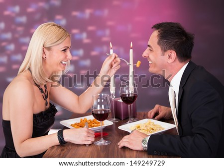 Romantic Young Couple Having Dinner At Restaurant - stock photo