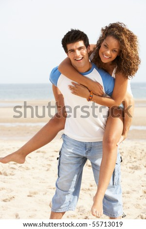 Romantic Young Couple Having Piggyback Fun On Beach
