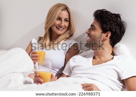 Romantic young couple in bed at home drinking orange juice. - stock photo