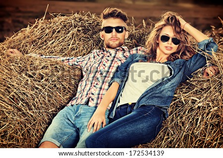 Romantic young couple in casual clothes sitting together in haystack. - stock photo