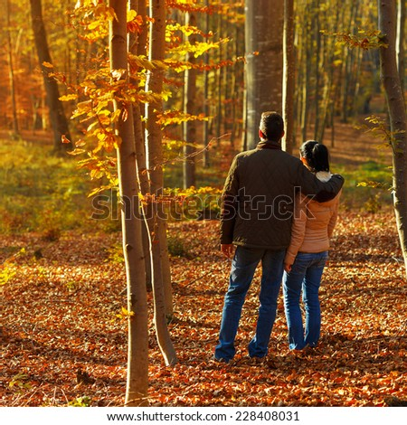 Romantic young couple in forest looking to the sunset in autumn season - stock photo